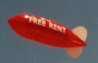 helium advertising blimp balloon with Free Rent lettering